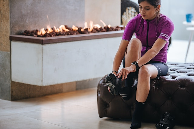 A Young Lady Puts on Cycling Shoes in Front of a Modern, Wide, Electric Fireplace