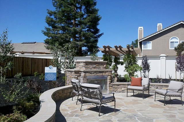 Outdoor stone patio with fireplace and chairs