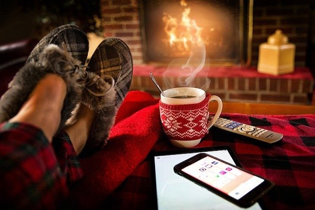 A person relaxing in a chair in front of a fireplace with slippers on and next to his coffee and cell phone on a table.