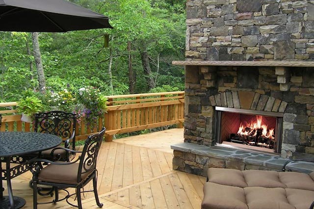 An outdoor deck featuring a fireplace, lounge chairs, and a table with trees in the background.