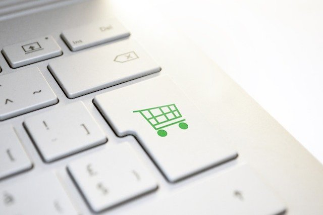 A silver computer keyboard with a shopping basket button