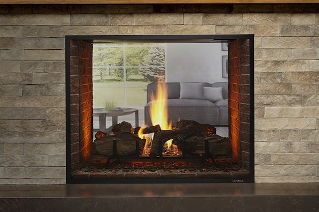 A photo of a Heat & Glo Fireplaces see-through gas fireplace placed in a grey brick wall.