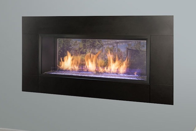 A photo of a Monessen Hearth Artisan See-Through Vent Free Gas Fireplace mounted in a grey wall.