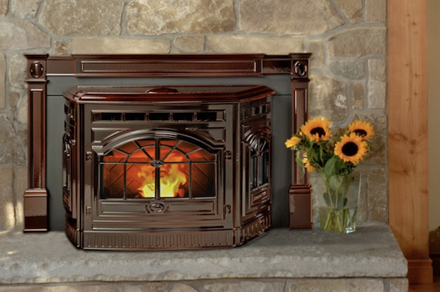 A Quadra-Fire Castile Pellet Insert with a fire blazing inside of it, with sunflowers in a vase next to it.