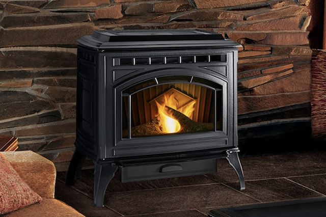 A Quadra-Fire Classic Bay 1200 Pellet Stove in a beige-colored room on dark stained wood flooring.